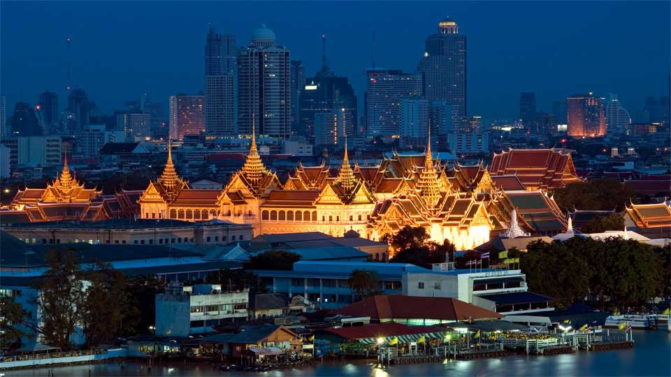 A wat lit up in gold light against the backdrop of Bangkok's skyline.