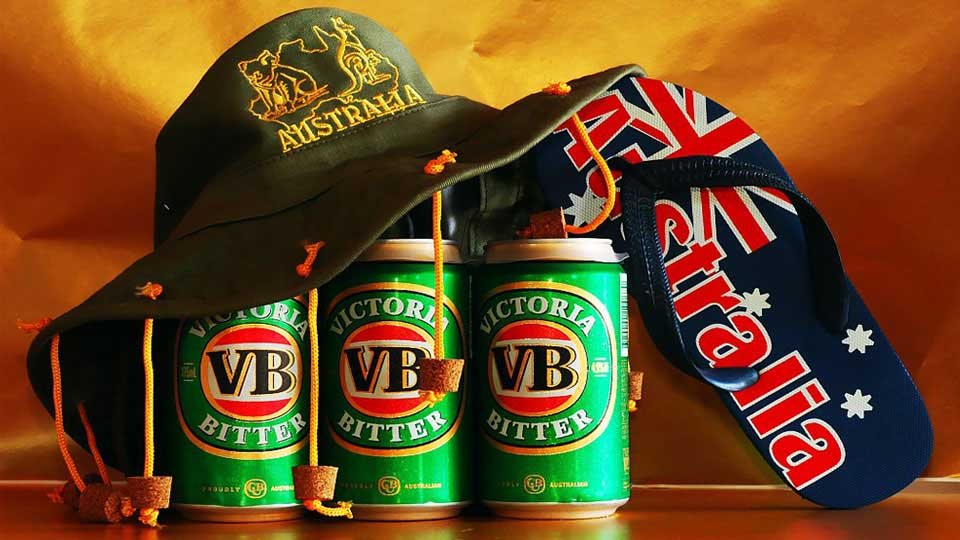 "Hat with Corks Hanging From The Brim On a Six Pack of Beer and a Sandal Marked ""Australia"""