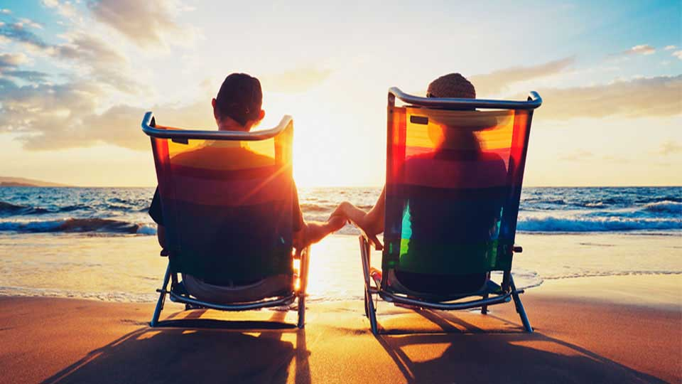A couple holding hands, relaxing in lawn chairs on the beach at dawn or dusk.